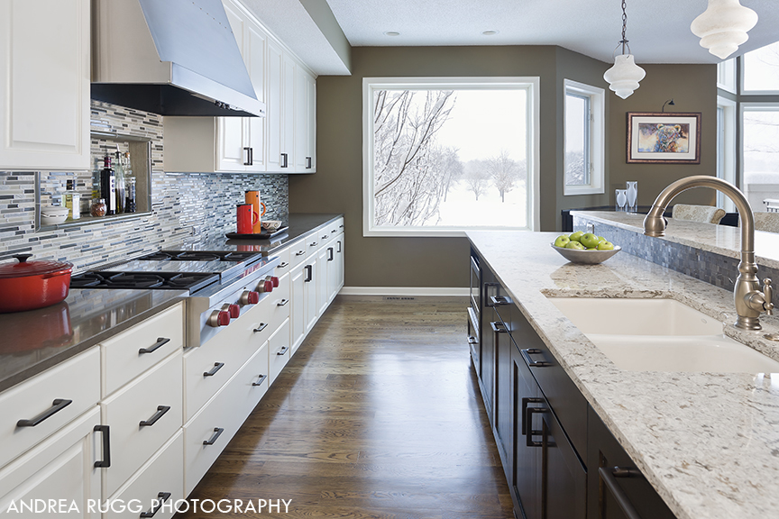 View of high end kitchen showing white cabinets and dark wood island